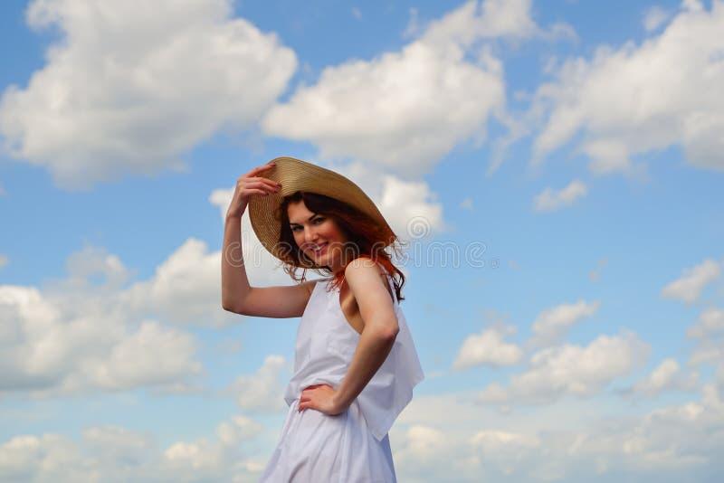 Szczęśliwa piękna dziewczyna w biel sukni, kapeluszowym ono uśmiecha się, niebieskie niebo i chmury na tle, fotografia royalty free
