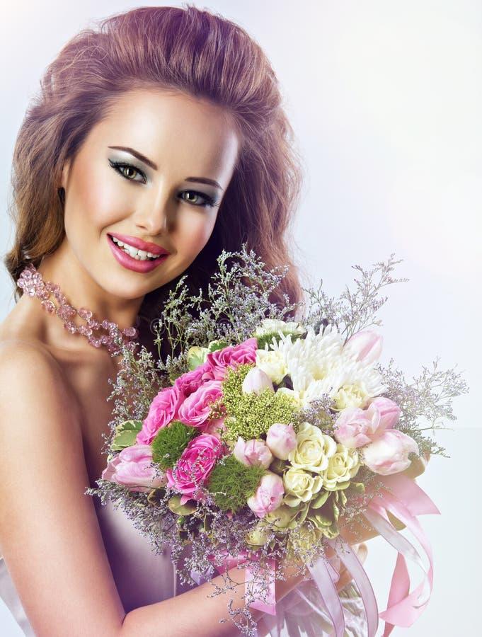 Szczęśliwa piękna dziewczyna z kwiatami w rękach zdjęcie stock