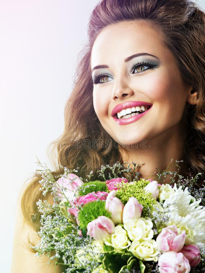 Szczęśliwa piękna dziewczyna z kwiatami w rękach zdjęcie royalty free