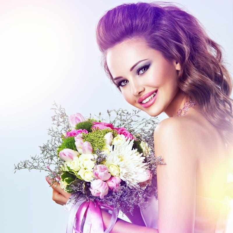 Szczęśliwa piękna dziewczyna z kwiatami w rękach zdjęcia royalty free