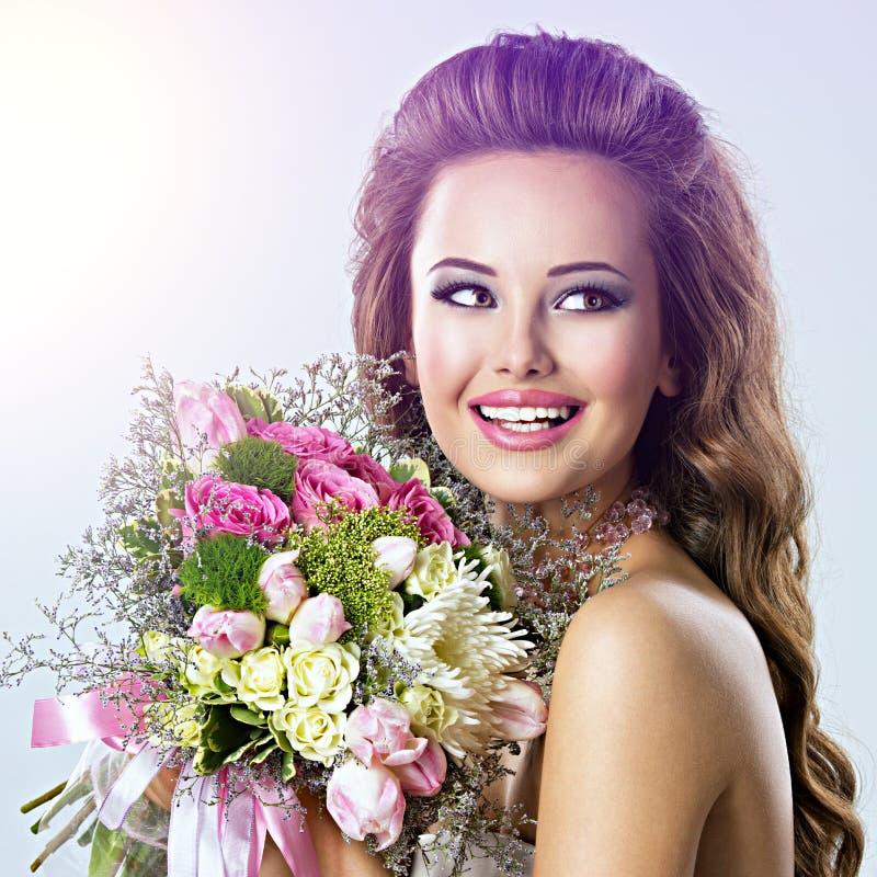 Szczęśliwa piękna dziewczyna z kwiatami w rękach obrazy royalty free