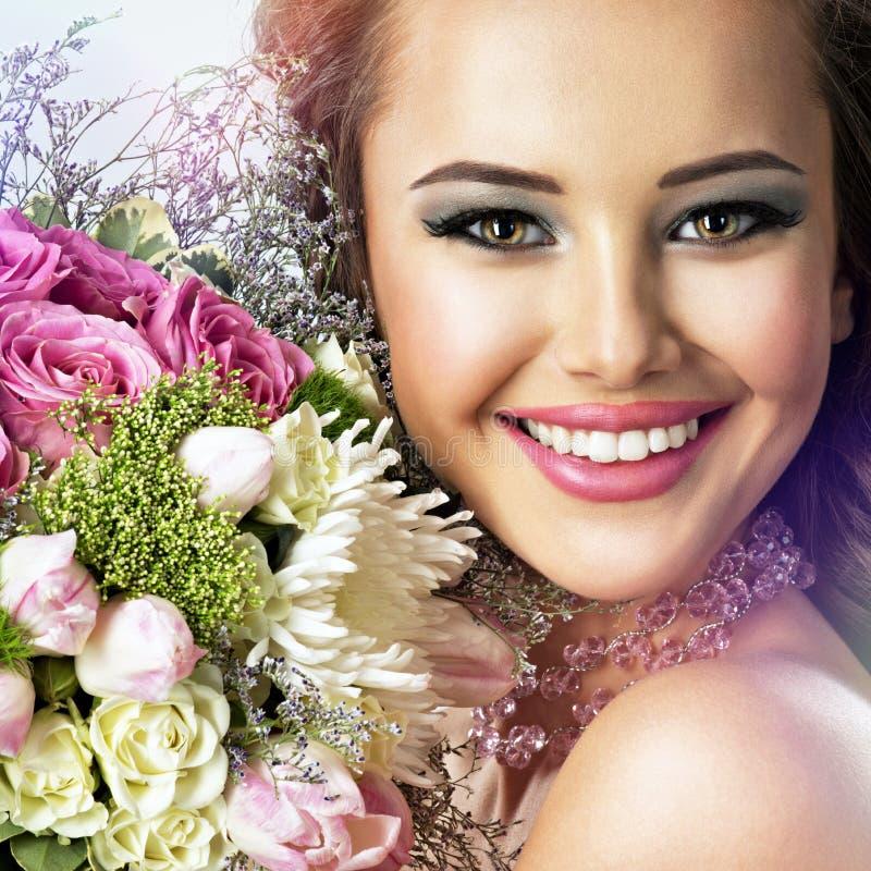 Szczęśliwa piękna dziewczyna z kwiatami w rękach fotografia stock