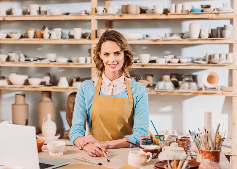 szczęśliwa piękna garncarka z ceramiką i laptopem fotografia royalty free