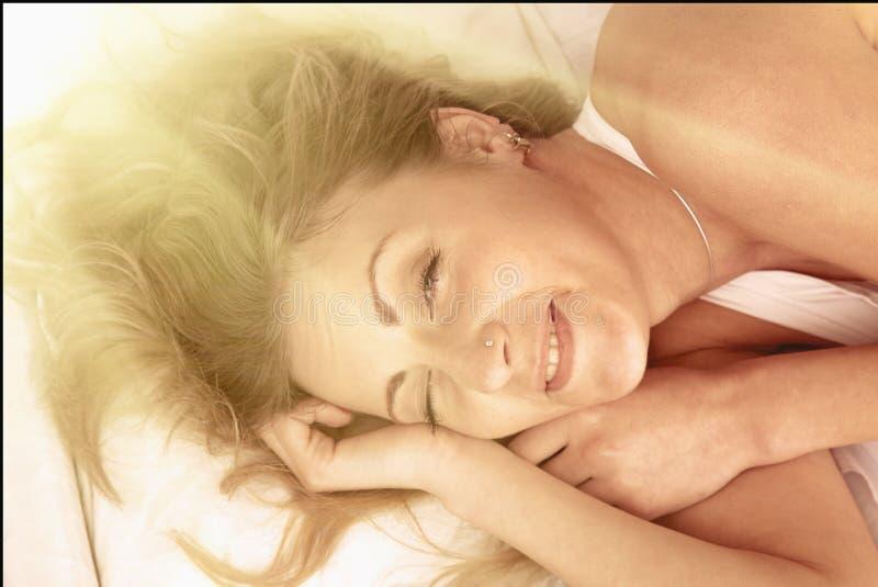 Szczęśliwa piękna kobieta budzi się up w jej łóżku fotografia royalty free