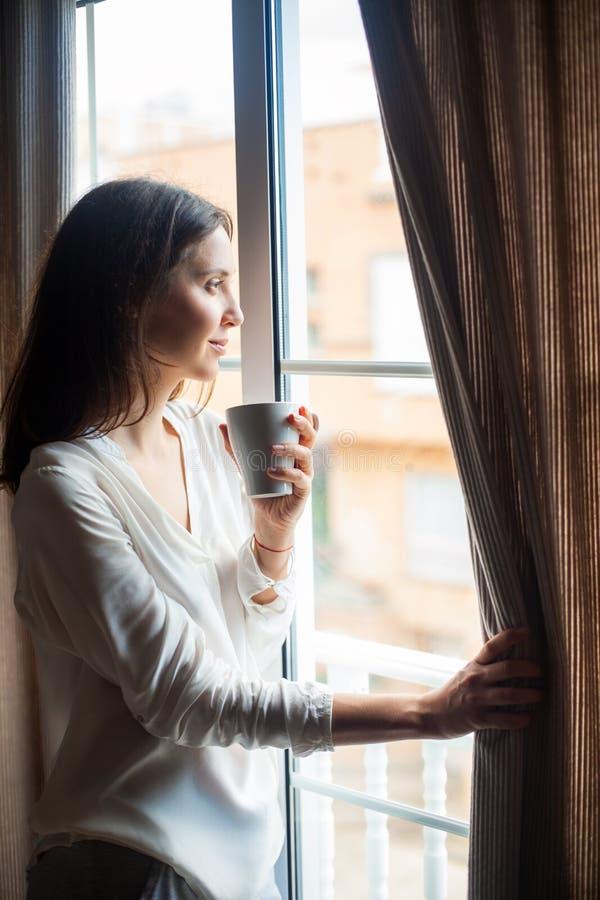 Szczęśliwa piękna kobieta pije gorący kawowy patrzeć na okno przy h obraz stock