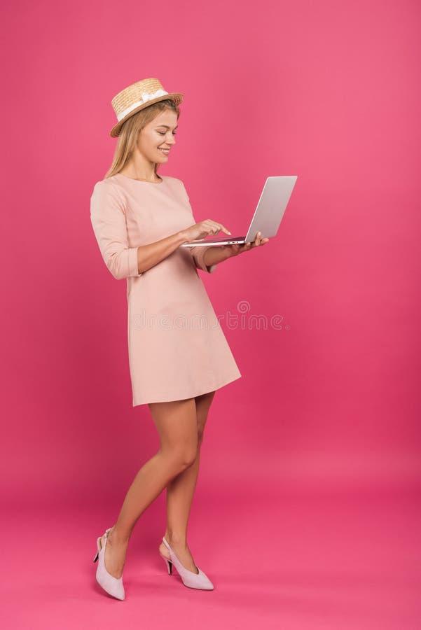 szczęśliwa piękna kobieta pisząca na laptopie, odizolowana fotografia stock