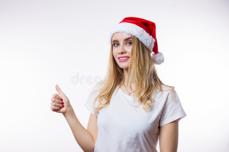 Szczęśliwa piękna kobieta w czerwonych Santa kapeluszowych przedstawień szyldowym kciuku na w górę białego tła z kopii przestrzen fotografia royalty free