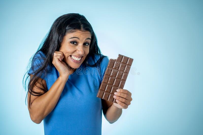 Szczęśliwa piękna młoda łacińska kobieta trzyma dużego baru czekolada z szalonym z podnieceniem twarzy wyrażeniem w cukrowym nało obrazy stock