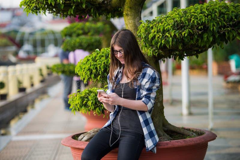 Szczęśliwa piękna młoda Kaukaska szkoły średniej dziewczyna z mądrze telefonem outdoors na pogodnym letnim dniu texting i ono uśm zdjęcie royalty free