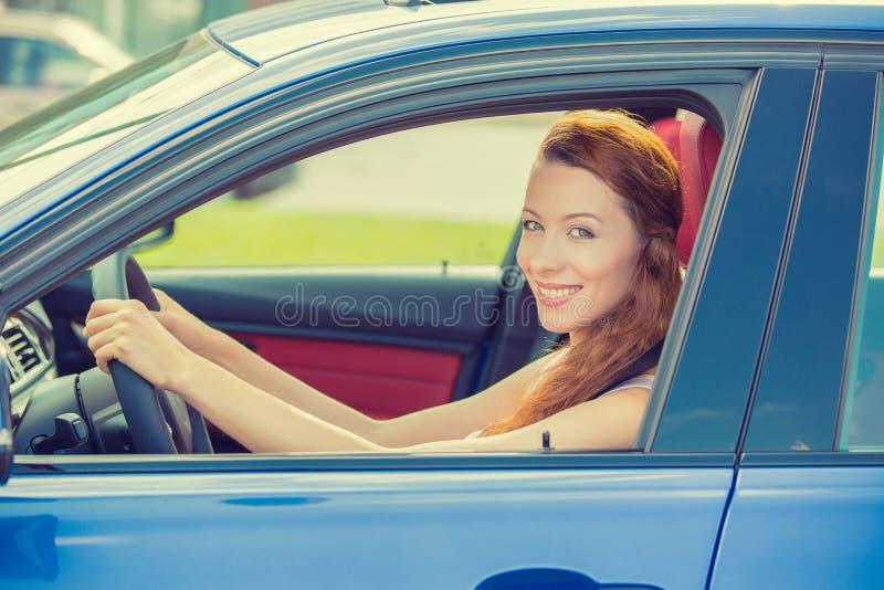 Szczęśliwa piękna młoda kobieta jedzie jej nowego błękitnego samochód zdjęcia royalty free