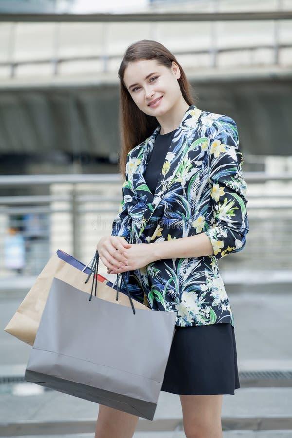 Szczęśliwa piękna młoda kobieta z torbami na zakupy cieszy się na ulicie w mieście dziewczyna modna obraz royalty free