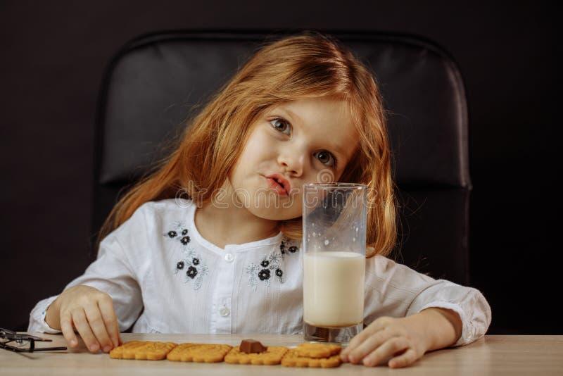Szczęśliwa piękna mała dziewczynka ma przekąskę z mlekiem i ciastkami zdjęcie royalty free