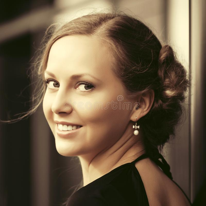 Szczęśliwa piękna mody kobieta z babeczki updo fryzurą na miasto ulicie obraz royalty free