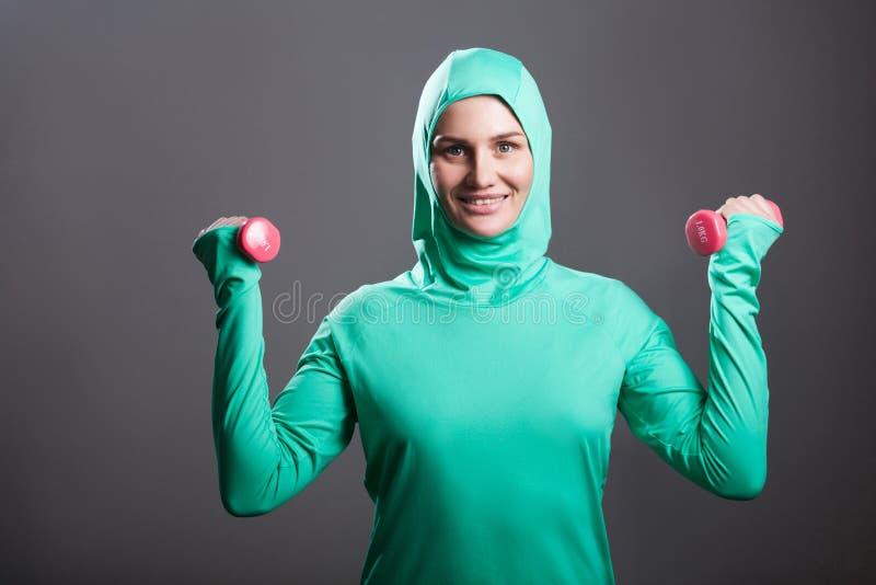 Szczęśliwa piękna muzułmańska kobieta w zielonym hijab lub islamskim sporta wea fotografia royalty free