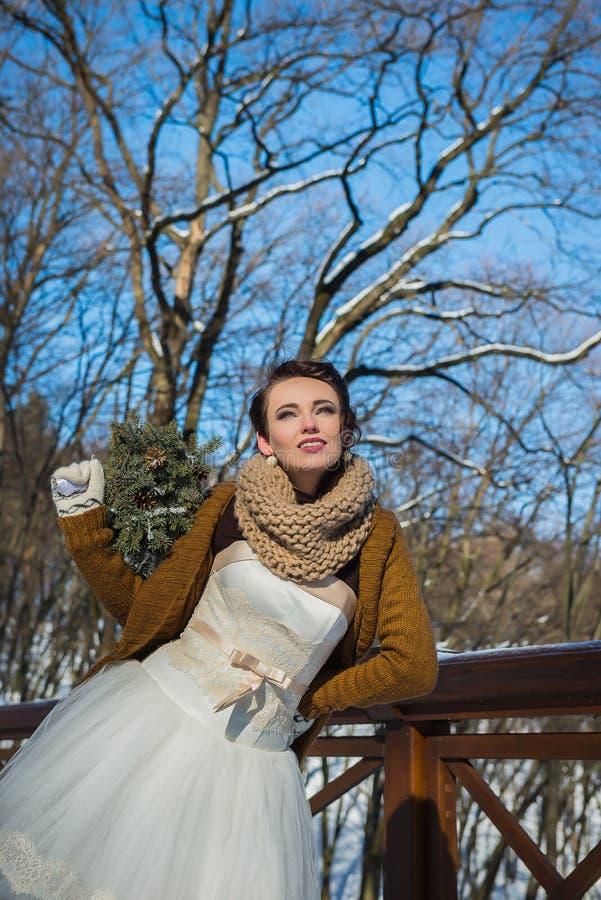 Szczęśliwa piękna panna młoda w śnieżnym zima dniu pogodna pogoda elegancki z ślubu bukietem robić od chojaka ręcznie robiony mit zdjęcia royalty free