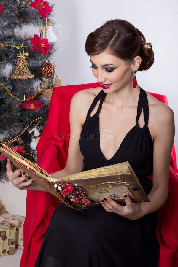 Szczęśliwa piękna seksowna kobieta w wieczór sukni z makijażem i fryzurą siedzi blisko choinki z magiczną książką w Nowym Yea fotografia stock