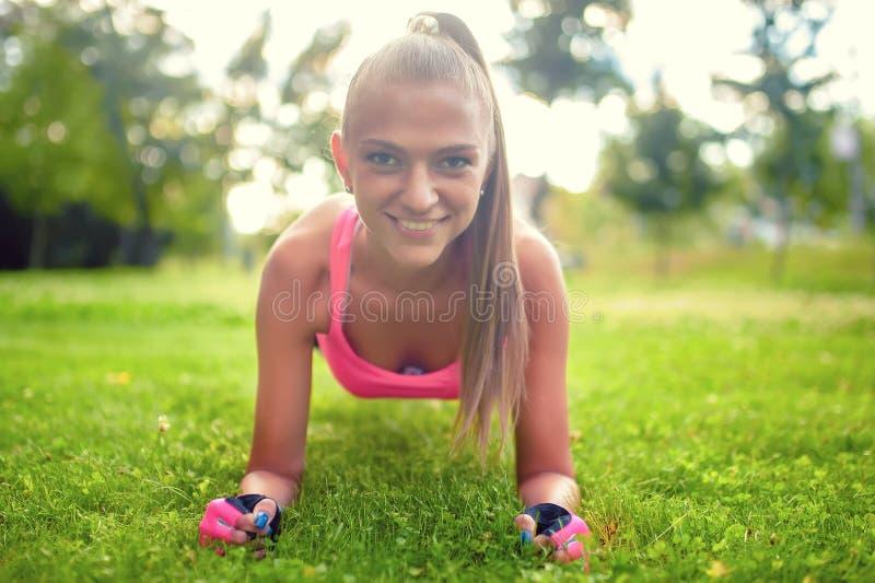 Szczęśliwa, piękni blondynki dziewczyna robi abs, i isometry na trawie fotografia royalty free