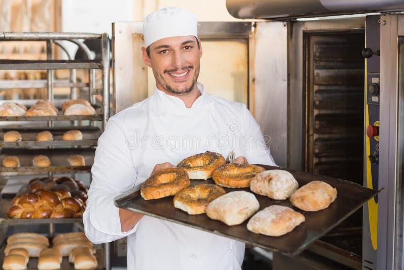 Szczęśliwa piekarniana pokazuje taca świeży chleb zdjęcia stock