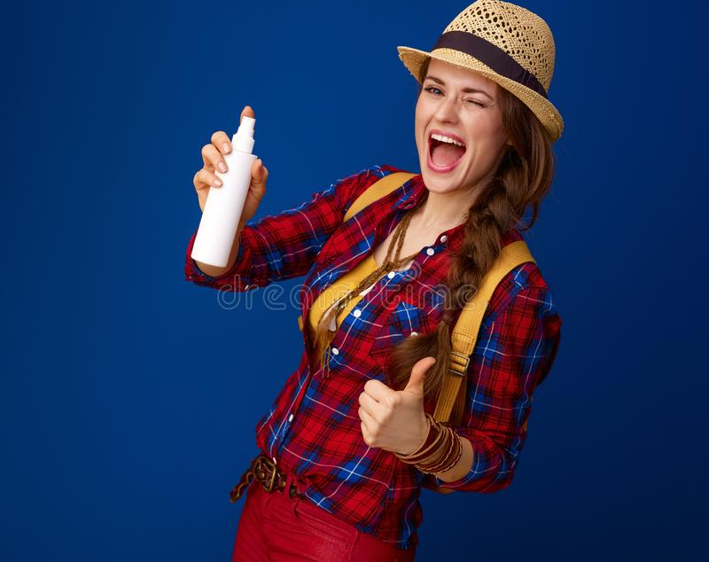 Szczęśliwa podróżnicza kobieta pokazuje aprobaty pokazuje butelkę kiść obraz stock