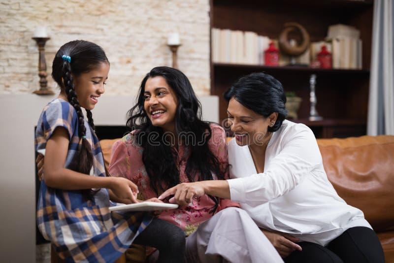 Szczęśliwa pokolenie rodzina używa cyfrową pastylkę wpólnie w domu obraz stock