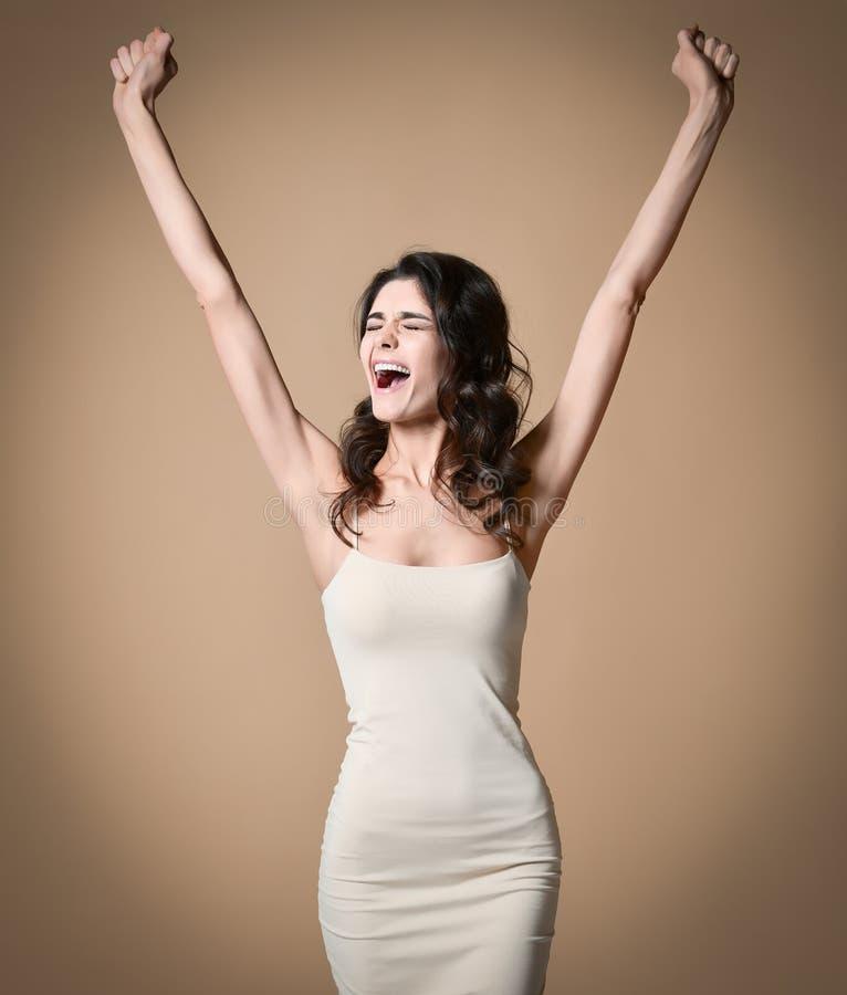 Szczęśliwa pomyślna młoda kobieta krzyczy sukces i świętuje z nastroszonymi rękami obrazy stock