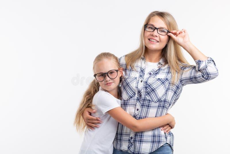 Szczęśliwa potomstwo matka i roześmiany dzieciak w mod szkłach zabawę na białym tle obrazy stock