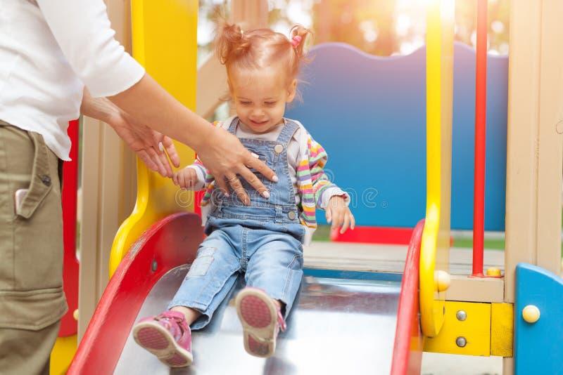 Szczęśliwa potomstwo matka z jej dziewczynką bawić się w kolorowym boisku dla dzieciaków Mama z berbeciem ma zabawę przy lato par obraz royalty free