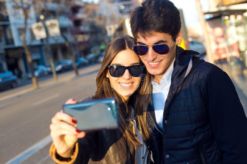 Szczęśliwa potomstwo para bierze selfies z smartphone fotografia stock
