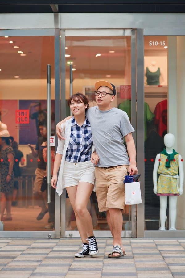 Szczęśliwa potomstwo para chodzi out Uniqlo sklep, Pekin, Chiny obraz royalty free
