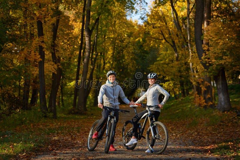 Szczęśliwa potomstwo para iść dla rower przejażdżki na jesień dniu w parku zdjęcia royalty free