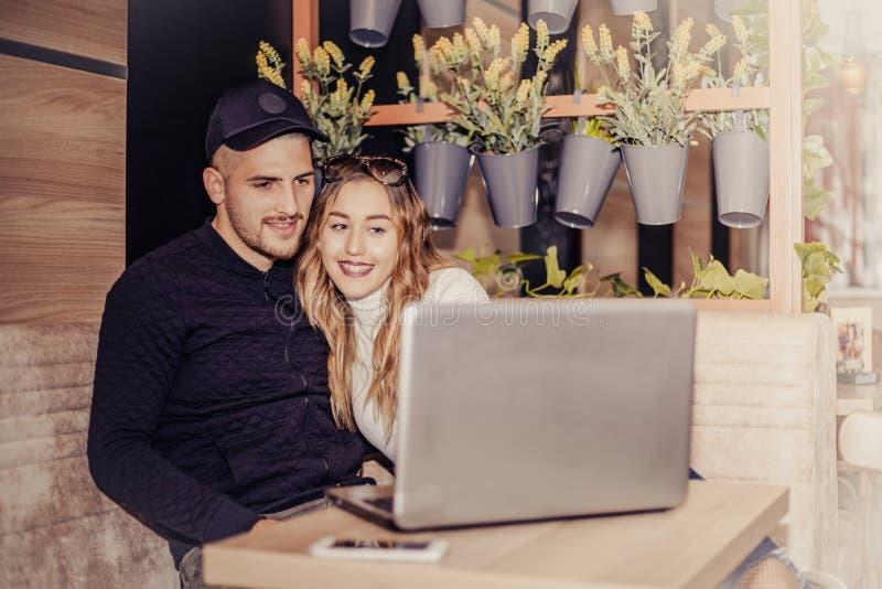 Szczęśliwa potomstwo para używa laptop przy kawiarnią obraz royalty free