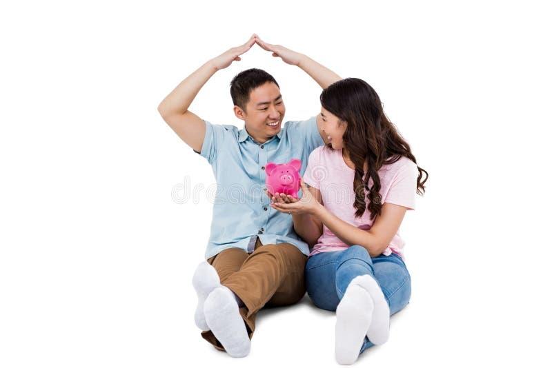 Szczęśliwa potomstwo para z prosiątka bakiem obrazy stock