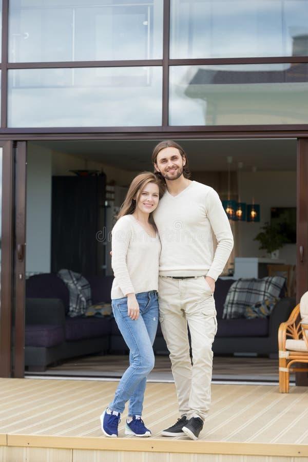 Szczęśliwa potomstwo pary pozycja na nowym luksusu domu tarasie, portrai zdjęcie royalty free
