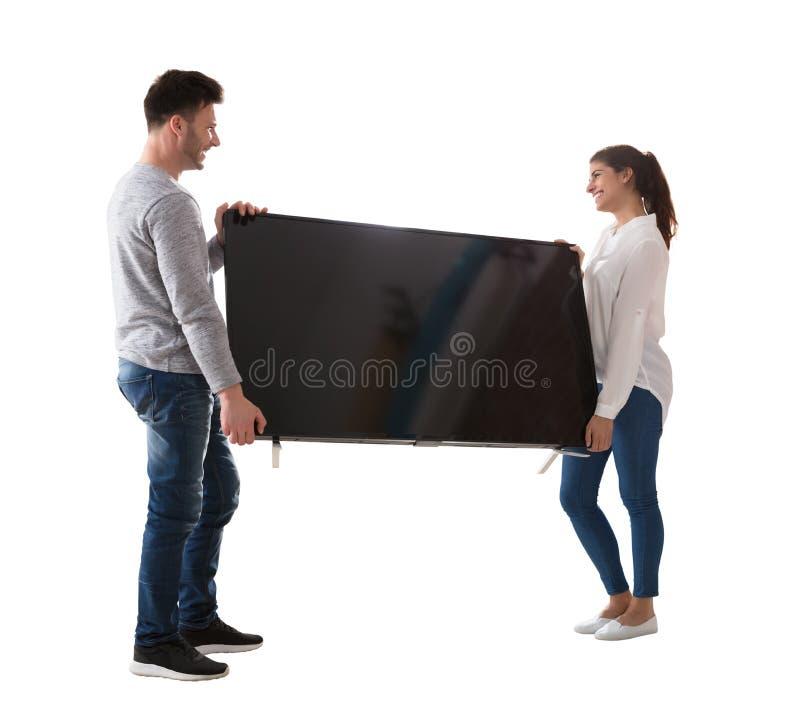 Szczęśliwa potomstwo pary przewożenia telewizja zdjęcie royalty free
