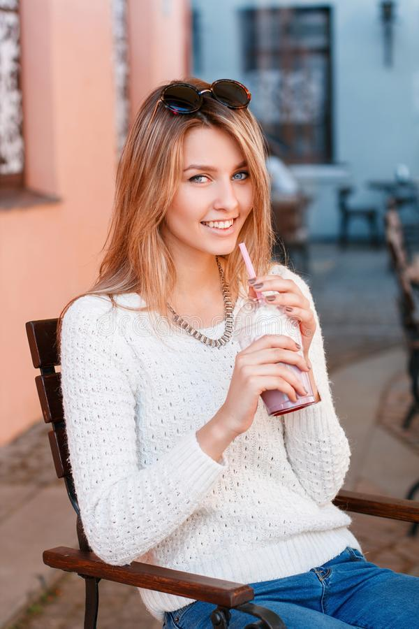 Szczęśliwa powabna młoda modniś kobieta z pięknym uśmiechem w trykotowym pulowerze w cajgach z okularami przeciwsłonecznymi obrazy stock