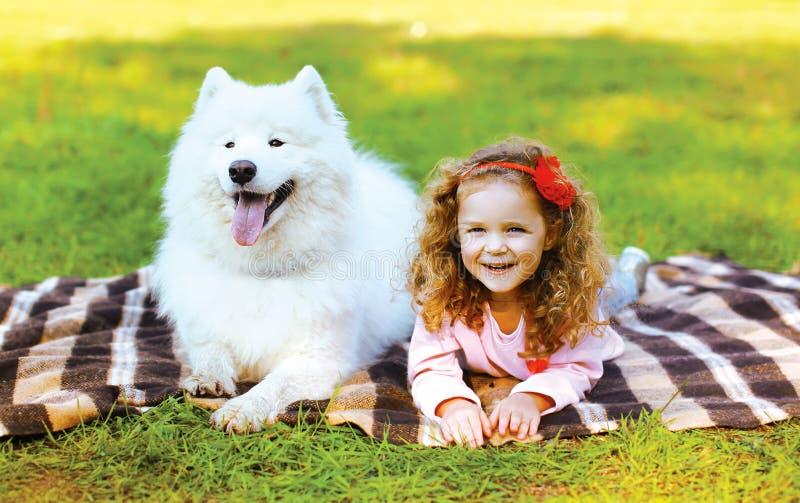 Szczęśliwa pozytywna mała dziewczynka i pies ma zabawę w pogodnej jesieni obraz stock