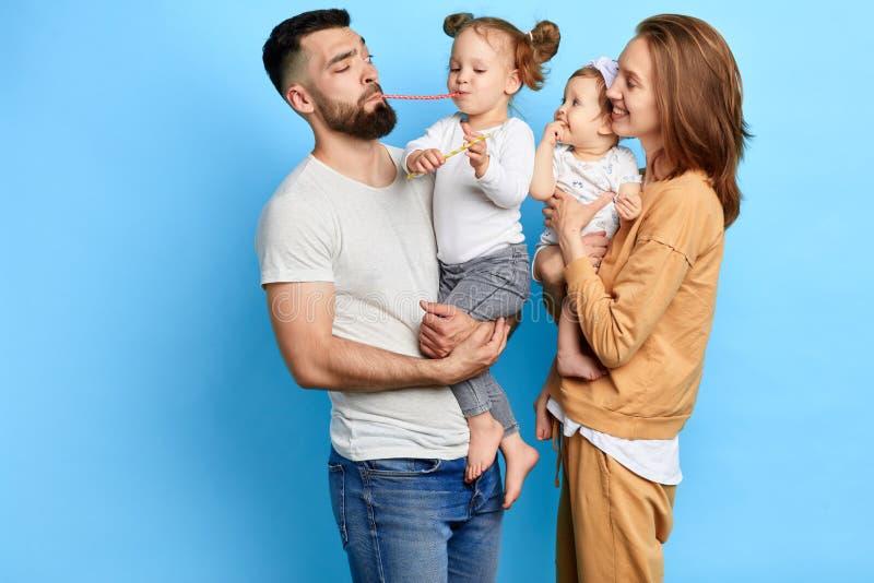 Szczęśliwa pozytywna rodzina i ich małe córki ma zabawę wpólnie zdjęcie stock