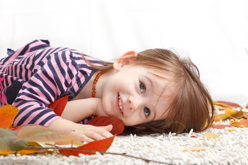 Szczęśliwa, pozytywna, uśmiechnięta dziewczyna, kłama na dywanie zdjęcia royalty free