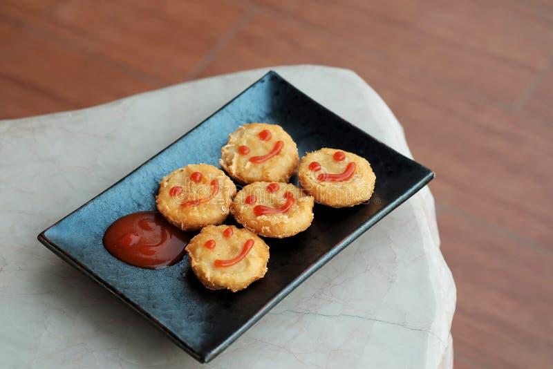 Szczęśliwa przekąska z kurczak bryłką z uśmiechu pomidorowym kumberlandem w czarnym talerzu zdjęcia stock