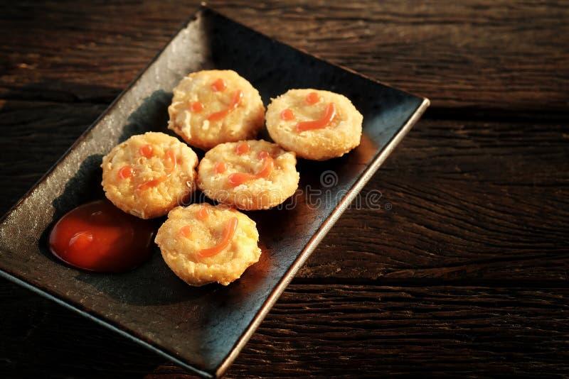 Szczęśliwa przekąska z kurczak bryłką z uśmiechu pomidorowym kumberlandem w czarnym talerzu na szorstki drewnianym obrazy royalty free