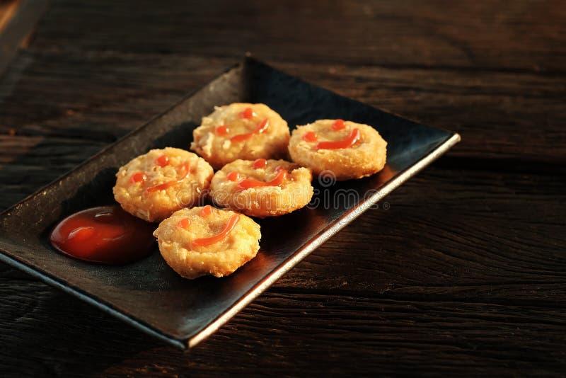 Szczęśliwa przekąska z kurczak bryłką z uśmiechu pomidorowym kumberlandem w czarnym talerzu na szorstki drewnianym zdjęcia stock