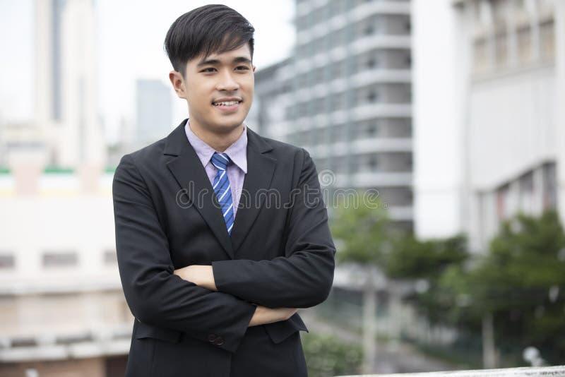 Szczęśliwa przystojna biznesmen pozycja i ono uśmiecha się przy plenerowym zdjęcie stock