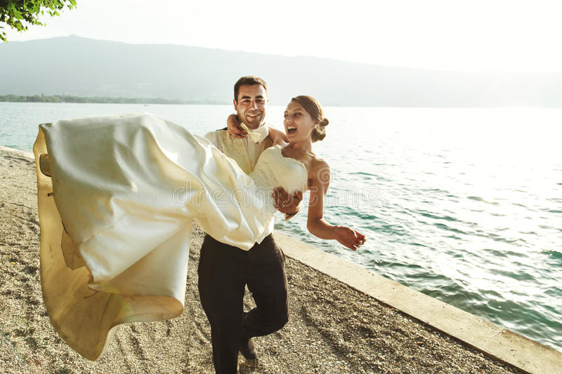 Szczęśliwa przystojna fornala mienia panna młoda w jego rękach na plaży przy sunse obraz royalty free