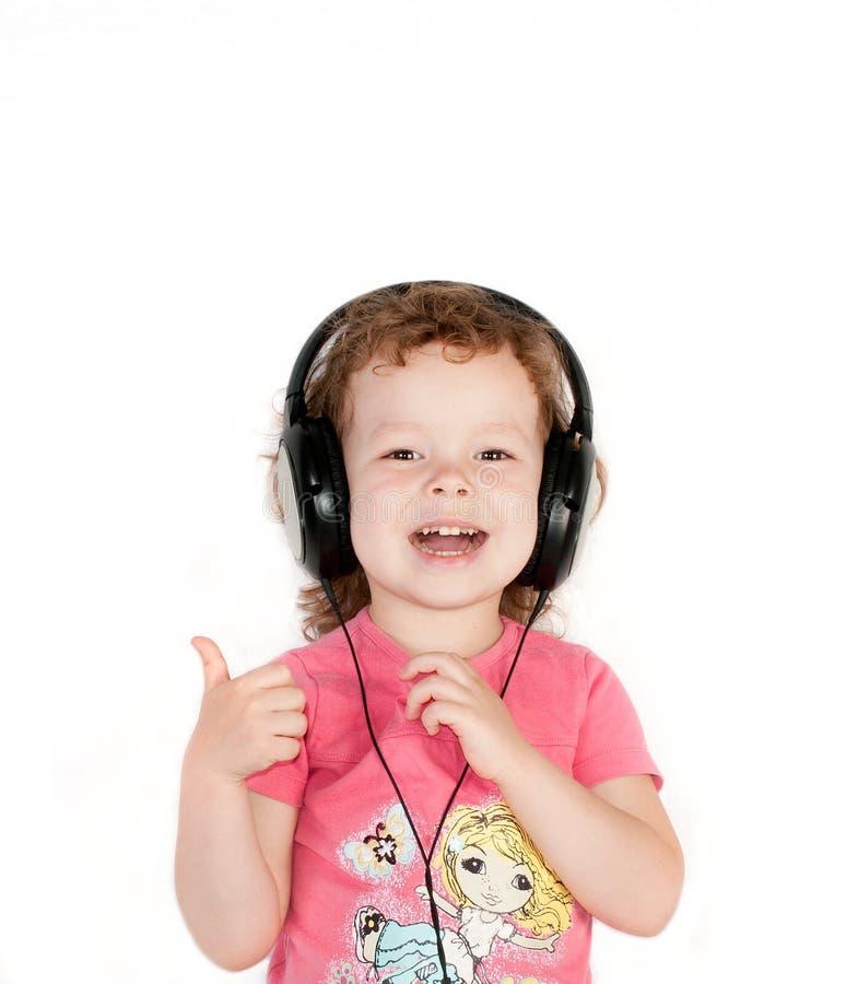 Szczęśliwa qute dziewczyna w hełmofonach zdjęcie royalty free