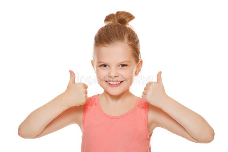 Szczęśliwa radosna mała dziewczynka ono uśmiecha się pokazywać aprobatę, odizolowywać na białym tle obrazy stock