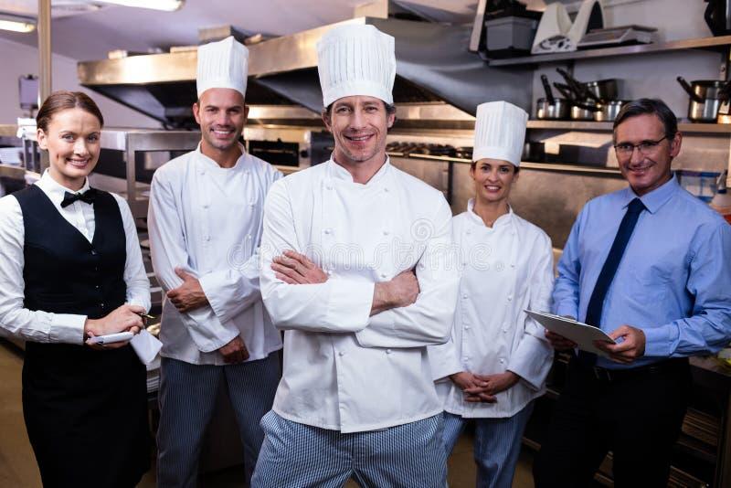 Szczęśliwa restauraci drużyna stoi wpólnie w handlowej kuchni fotografia royalty free