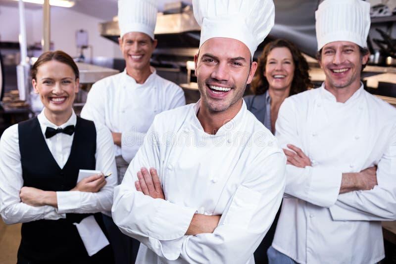 Szczęśliwa restauraci drużyny pozycja wraz z rękami krzyżował w handlowej kuchni zdjęcie royalty free