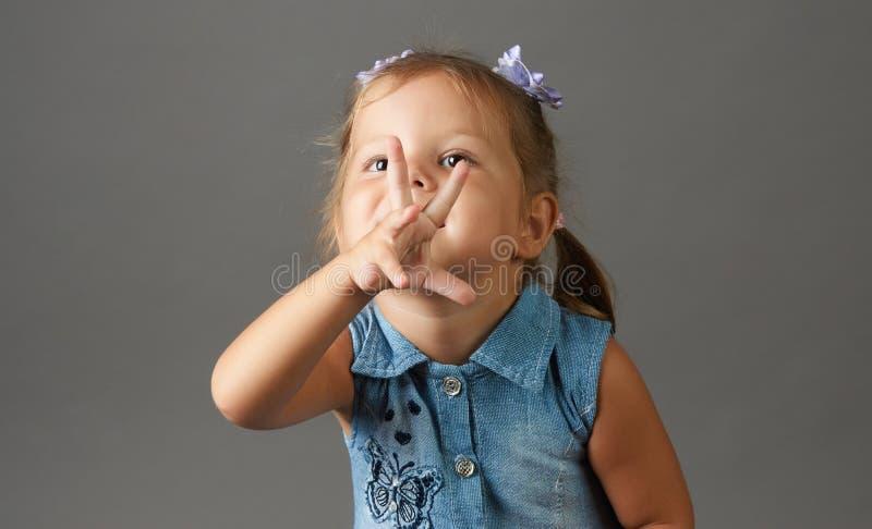 Szczęśliwa 3 roczniaka mała dziewczynka pokazuje trzy palca fotografia stock