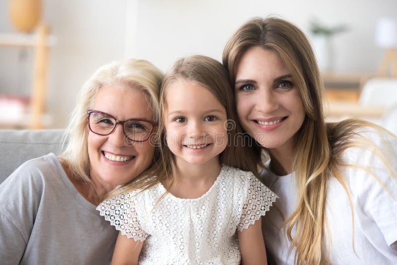 Szczęśliwa rodzina babcia, córka i dziecko patrzeje camer, obraz royalty free
