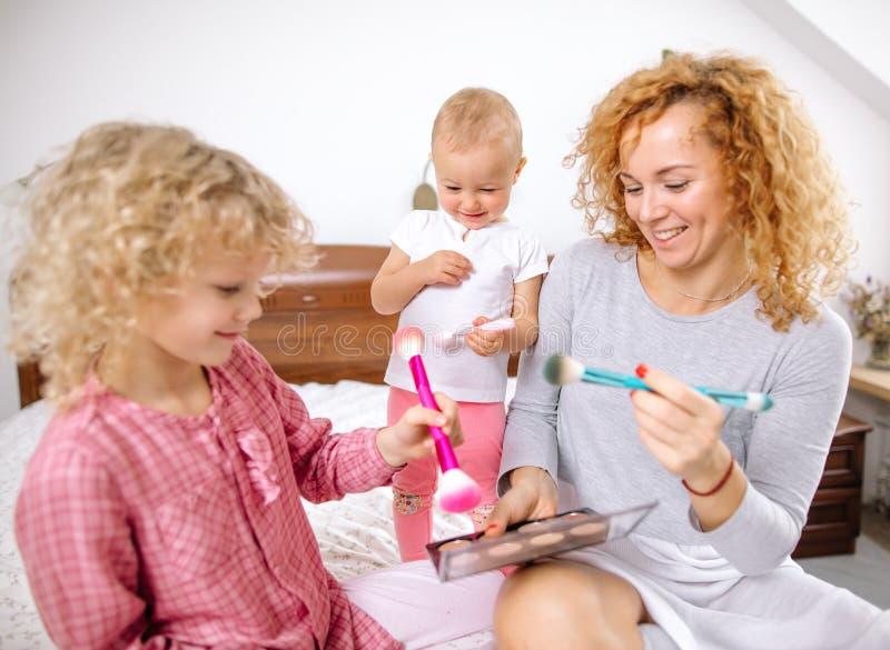 Szczęśliwa rodzina bawić się sztuczki w sypialni fotografia stock